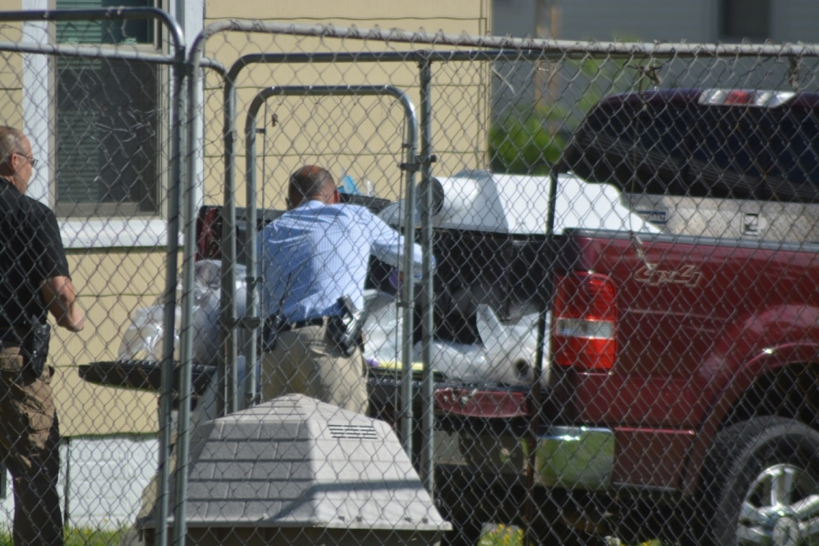 Investigators load items into a pickup Tuesday.