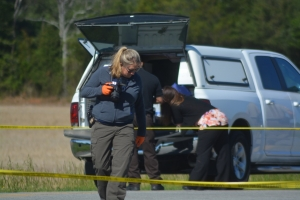 An SBI agent examines a portion of Macon Price Road near where the woman's body was located.