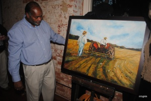 Hill shows his painting after its unveiling.